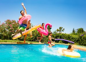 Happy,Friends,Jumping,In,Pool,On,The,Vacations
